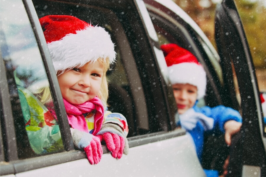 Kids in car with Christmas Hats Holiday road trip