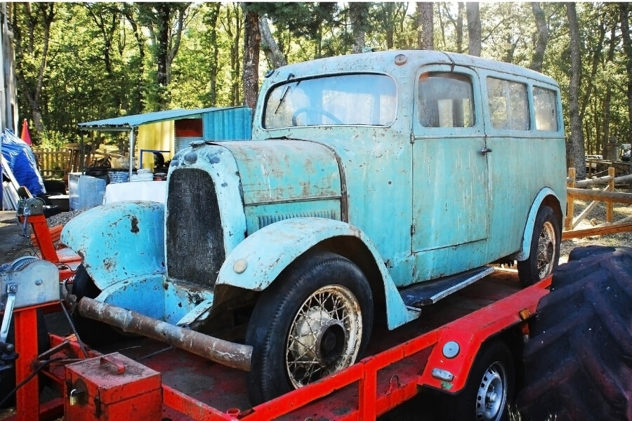 blue antique car being towed